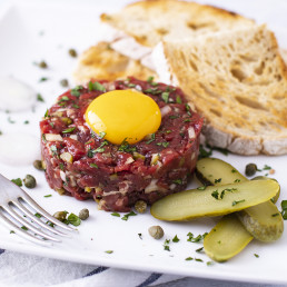 Food photography featuring a Ribeye Tartare served with pickled gerkins and toasted bread